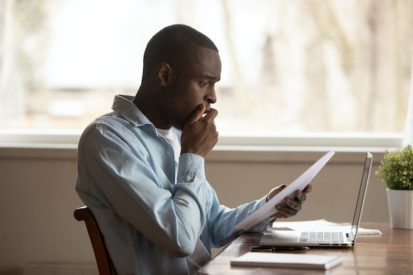 Upset unhappy young african american guy sitting at table, holding paper document, received bad news, dismissal notice, big debt notification or utility bill, financial problems, eviction notice.
